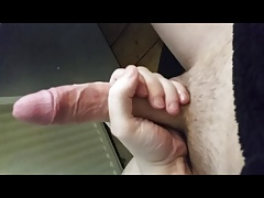 Guy strokes his massive uncut cock